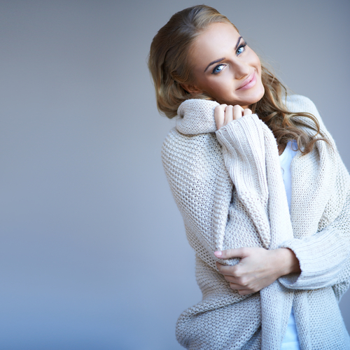 A beautiful smiling woman bundled up in an oversized tan sweater